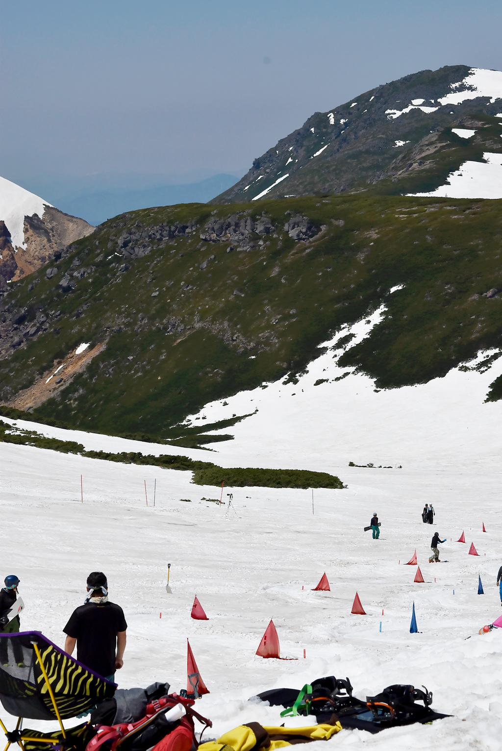 山肌に残る雪とスキー・スノボーする人